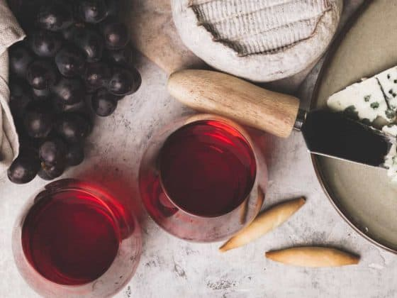 Red wine with charcuterie assortment on rustic concrete background